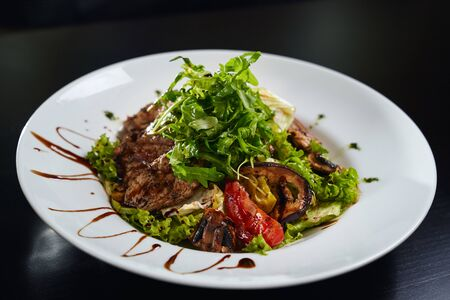 Close up of tasty fresh warm salad with grilled meat, avocado, grilled vegetables and mushrooms and lettuce. Top view of healthy dish served with brown sauce on white plate in restaurant. Standard-Bild