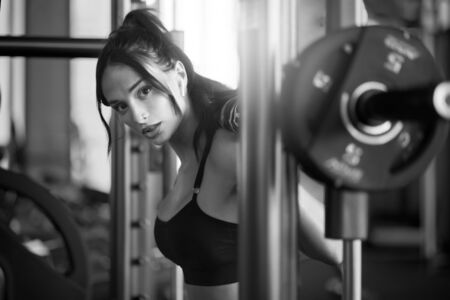 Side crop of brunette female bodybuilder using wireless headphones and doing squats in multipower smith machine, looking at camera. Srtong woman with slim body training legs in gym, black and white. Stock fotó