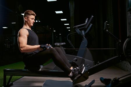 Muscular bodybuilder in sportswear training back sitting on exercise machine. Side view of man with perfect body building body in gym in dark atmosphere. Concept of bodybuilding, fitness.