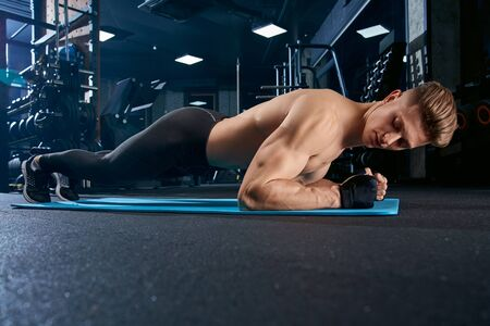 Muscular caucasian shirtless man training on floor on mat in sports club. Close up of young sportsman in gloves doing plank exercise in empty gym. Concept of bodybuilding.
