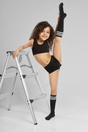 Portrait of adorable smiling girl in black sportswear and knee socks demonstraiting split while standing, isolated on gray background. Little female gymnast showing flexibility, leaning on staircase. 免版税图像