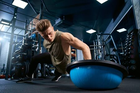 Front view of muscular caucasian man doing push ups on one hand on floor using balance half ball. Close up of young sportsman building muscles in empty gym. Concept of bodybuilding, sport.