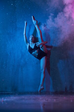 Young ballerina in black underwear and pointes doing splite while standing on socks near wall, loft interior. Pretty flexible slim wet artist posing. Isolated on blue with red light, rain and smoke.
