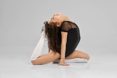 Side view of pretty girl in black sportswear and white knee socks posing on floor, isolated on gray studio background. Little female professional gymnast with curly hair showing flexibility, training.