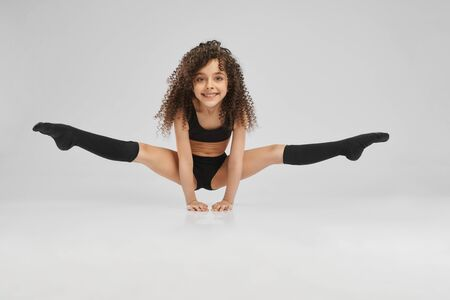 Little female professional gymnast doing split, standing on arms on floor, isolated on gray studio background. Smiling girl in black sportswear and knee socks with curly hair showing flexibility.