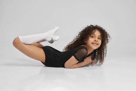 Cute smiling girl in sportswear and knee socks demonstraiting boat exercise, isolated on gray background. Little female professional gymnast with curly hair showing flexibility, looking at camera.