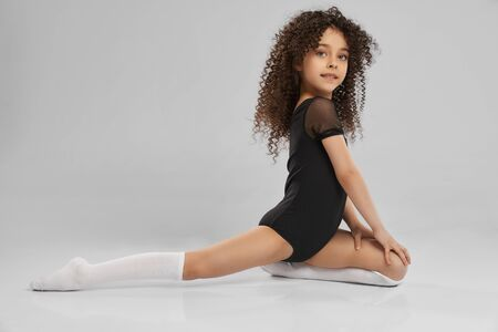 Side view of adorable smiling girl in black sportswear and knee socks doing half split, isolated on gray studio background. Little female professional gymnast with curly hair showing flexibility.