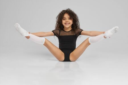 Young female professional gymnast sitting on floor with legs wide up, isolated on gray studio background. Smiling girl in black sportswear and knee socks with curly hair showing flexibility.