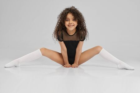 Smiling girl in black sportswear and knee socks with curly hair showing flexibility. Young female professional gymnast sitting on floor with legs wide, isolated on gray studio background.