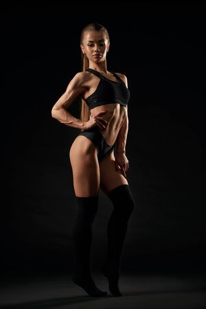 Full length side portrait of sexy caucasian female model with ponytail wearing black lingerie and knee socks standing on tiptoes, isolated on black. Fashionable woman with perfect body posing. Stock Photo