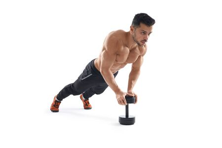 Muscular shirtless caucasian man training on floor using one dumbbell, isolated on white studio background. Close up of young sportsman building muscles, doing push ups. Concept of bodybuilding. 写真素材