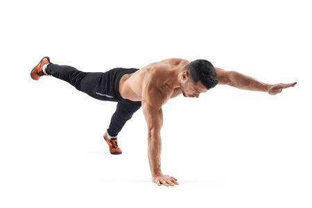Side view of young shirtless muscular bodybuilder in sportswear practicing Bird dog pose, working out indoor isolated on white studio background. Concept of healthy lifestyle, yoga.
