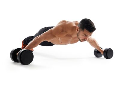 Muscular shirtless caucasian bidybuilder training on floor using dumbbells, isolated on white studio background. Close up of young sportsman building muscles, doing wide push ups. Concept of sport.