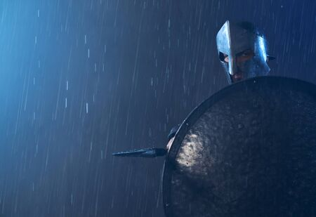 Portrait of spartan standing outdoors with spear and looking at camera. Front view of man in helmet hiding behind iron shield and pointing weapon in bad cloudy rainy weather. Ancient sparta concept. Foto de archivo