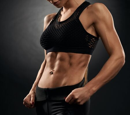 Side view of muscular incognito woman holding leggings and showing tensed abs. Isolated crop of pumped fitnesswoman in black sportswear posing on black studio background. Concept of sport, fitness. Zdjęcie Seryjne