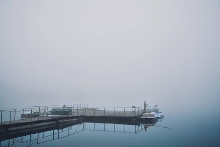 Human having hobby. Man standing on wooden berth in foggy morning and fishing. Fisherman engaged in fishing on pond and resting. Remotely view.