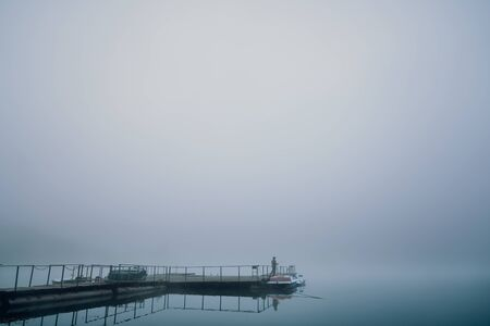 Fisher standing on wooden berth in morning and holding fishing rod. Grey fog over lake. Concept of hobby and relax.