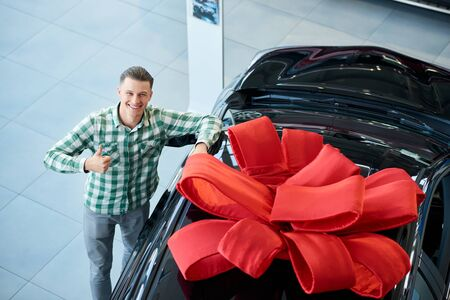 From above view of handsome smiling man standing near new car with huge red gift bow in dealership, gesturing and looking at camera. Young customer feeling happy, showing thumb up after purchase.
