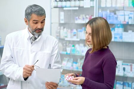 Female customer consulting with chemist in drugstore, holding blister pack of pills. Bearded pharmacist wearing lab coat, helping young woman in pharmacy with medicaments, explaining instruction.
