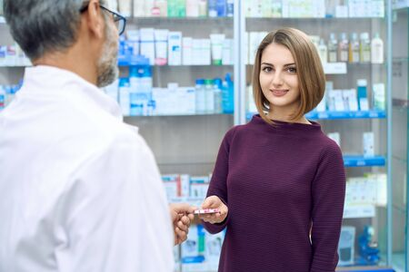 Portrait of satisfied female customer buying medicaments in drugstore and looking at camera. Crop of unrecognizable mature pharmacist offering woman medical products, giving blister pack of pills.