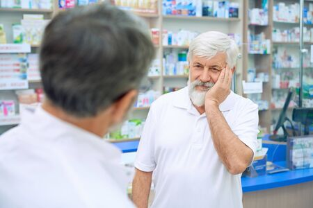 Selective focus of senior man with tooth ache consulting with pharmacist. Back view of unrecognizable man in white uniform offering medicineswhile eldery male customer frowning painfully.
