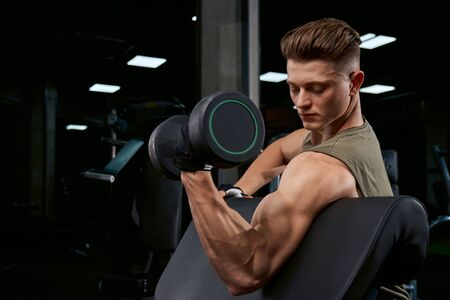 Close up of handsome bodybuilder training biceps with dumbbell on bench. Close up of muscular sportsman with perfect body posing in gym in dark atmosphere. Concept of bodybuilding.