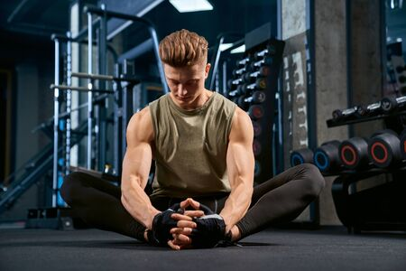 Close up of fit caucasian bodybuilder in sportswear doing butterfly stretch on floor in sports club. Front view of young sportsman posing in empty gym. Concept of bodybuilding, healthy lifestyle. 写真素材