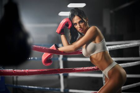Side view of brunette woman with strong face wearing red boxing gloves, underwear and leaning on rope. Young female fighter posing in empty gym, looking at camera and holding head. Concept of boxing. 版權商用圖片