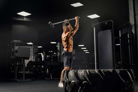 Side view of strong muscular man hitting giant tire with sledgehammer. Motion of shirtless caucasian bodybuilder building muscles in gym in dark atmosphere. Concept of crossfit, sport.