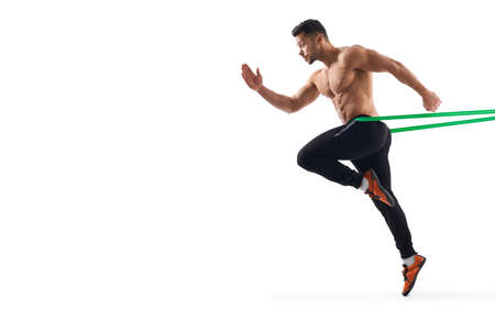 Side view of shirtless muscular bodybuilder running in place using resistanve band. Sportsman with perfect body posing, isolated on white studio background. Concept of bodybuilding.