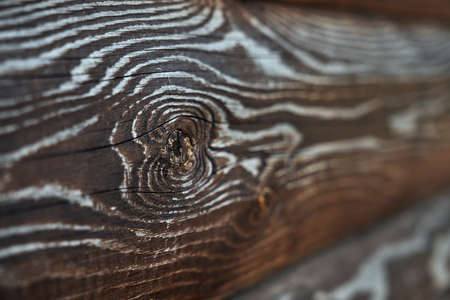 Rustic texture on wall outdoors, side view, dark background. Selective focus of brown old volume rough wooden planks, amazing natural pattern for design and decoration. Concept of natural decor.