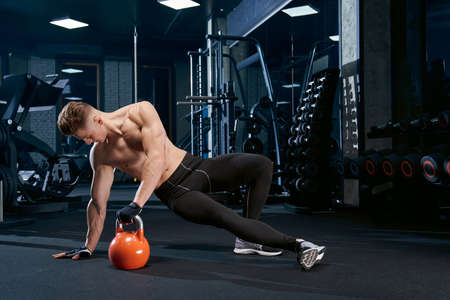 Muscular caucasian shirtless man training on floor in sports club. Close up of young sportsman in gloves doing side plank exercise, holding weights in hand in gym. Concept of bodybuilding.