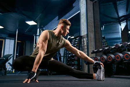 Muscular caucasian bodybuilder in sportswear stretching on floor in sports club. Front view of handsome young sportsman posing in empty gym. Concept of bodybuilding, healthy lifestyle.
