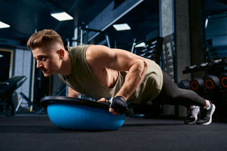 Muscular caucasian man training on floor using balance half ball in sports club. Close up of young sportsman building muscles, doing push ups in empty gym. Concept of bodybuilding. 写真素材