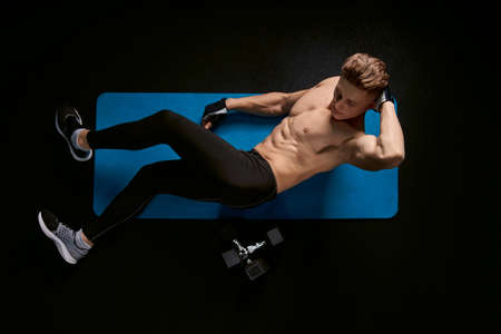Muscular caucasian man training abs on floor in sports club. From above view of handsome young sportsman building core muscles, doing crunches on mat in dark atmosphere. Concept of sport.