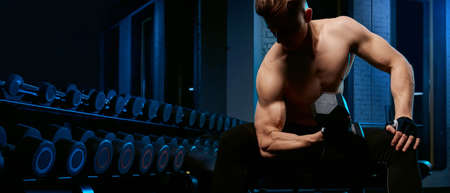 Crop of shirtless bodybuilder training biceps with dumbbell on bench. Close up of muscular sportsman with perfect body posing in gym in dark atmosphere. Concept of bodybuilding.
