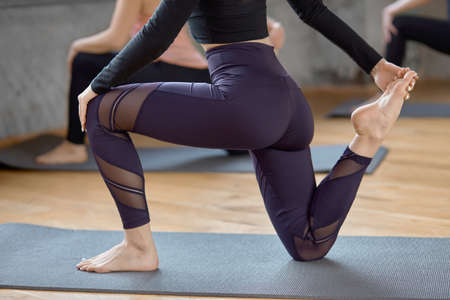 Crop of young fit women doing Horse rider exercise, anjaneyasana pose in spacy gym, loft interior. Side view of group of unrecognizable girls in sportswear working out yoga on mats in fitness hall.