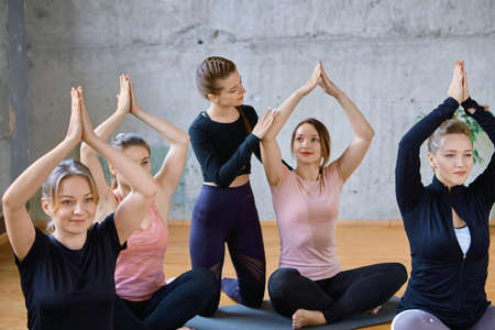 Front view of group of girls working out yoga on mats in hall. Selective focus of young fit female instructor helping women in sportswear sitting in Padmasana, lotus pose with hands up in spacy gym. Standard-Bild
