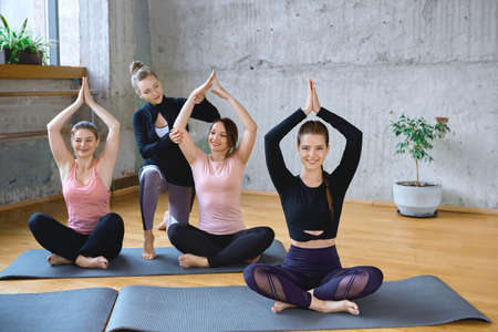 Front view of group of three girls working out yoga on mats in hall. Young fit female trainer helping women in sportswear sitting in lotus pose with hands up in spacy gym with windows. Loft interior.