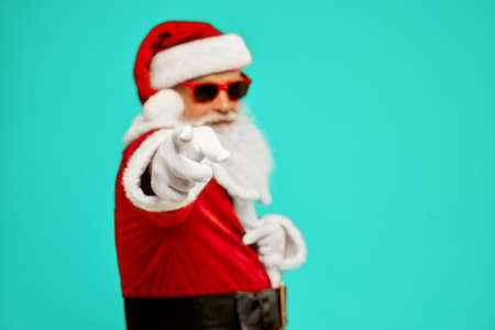 Side view of selective focus on finger of man in Santa Claus costume. Isolated portrait of senior male with white beard in sunglasses pointing at camera on blue studio background. Concept of holidays.