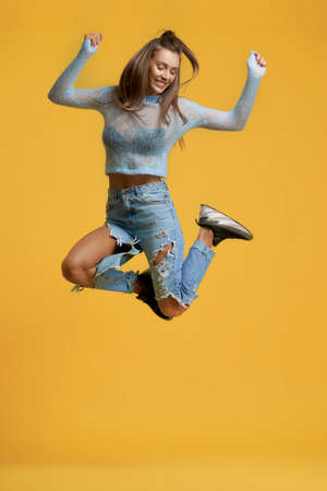 Front view of stylish lady in ripped jeans making jump and smiling. Joyful pretty girl looking down and raising hands. Isolated on yellow studio background. Concept of energy and freedom.