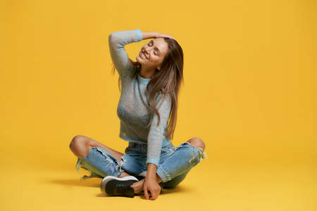 Front view of stylish lady sitting with crossed legs and smiling. Attractive young woman in ripped jeans closing eyes and touching hair. Isolated on yellow studio background. Concept of beauty and joy