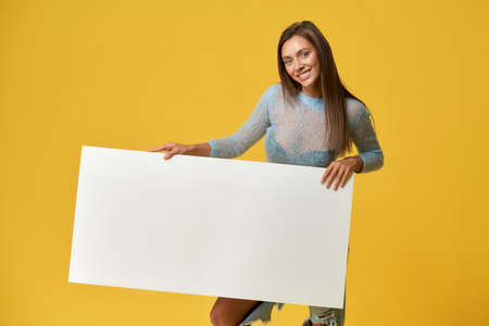 Front view of cheerful young woman holding white mock up placard for media banner. Pretty lady looking at camera and smiling. Isolated on yellow studio background. Concept of creativity and design.