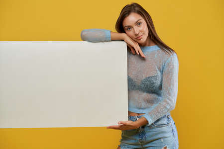 Front view of smiling pretty lady demonstrating cardboard blank poster. Charming young woman looking at camera and resting head on hand. Isolated on yellow studio background. Concept of advertising.