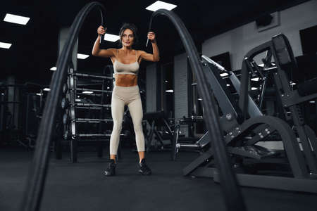 From below view of young brunette sportswoman in beige sportswear training in empty gym with ropes. Portrait of attractive young fitnesswoman with strong face doing cardio. Concept of sport.