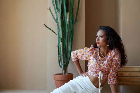 Portrait of mulatto girl with long black curly hair posing on floor near big cactus and wooden wheel. Stunning half african brunette wearing blouse with floral print, white skirt and seashells.