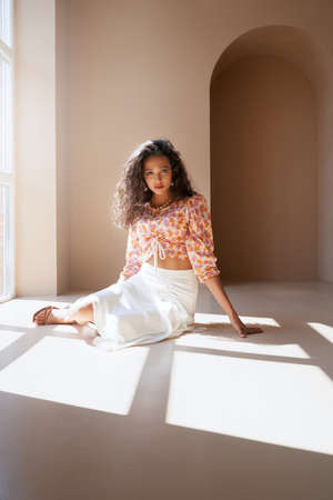 Front view of gorgeous half african young brunette model wearing fashionable summer outfit looking at camera. Mulatto girl with long black curly hair posing under sunlight on floor near big window.