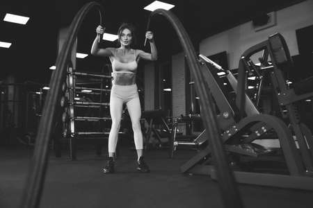 From below view of brunette woman in light sportswear training in empty gym with ropes. Monochrome full length portrait of attractive fitnesswoman with strong face doing cardio. Concept of sport. Standard-Bild