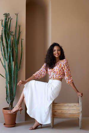 Laughing mulatto girl with long black curly hair posing near tall plant, sitting on big wooden wheel. Stunning happy half african female model wearing fashionable clothes and looking at camera.