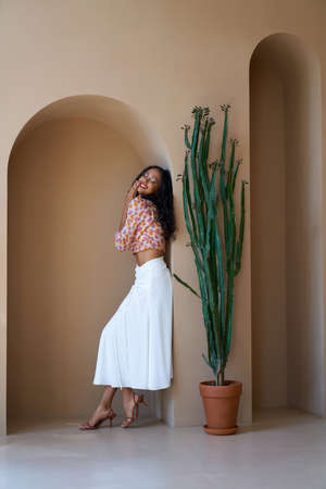 Side view of attractive smiling half african girl with black curly hair posing near tall cactus in pot indoors. Stunning mulatto brunette wearing blouse, skirt and sandals on heels standing near wall.